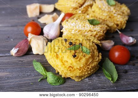 Raw pasta with cheese and vegetables on wooden background