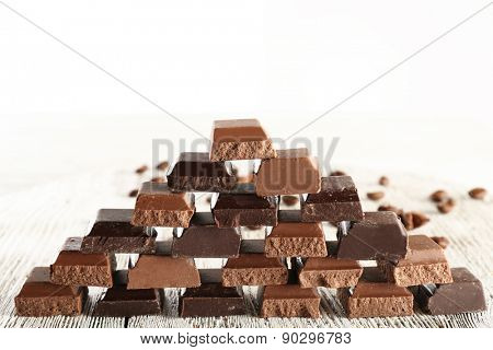 Pyramid of squared chocolate on wooden table isolated on white