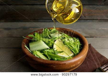 Poring green salad with olive oil on wooden table, closeup