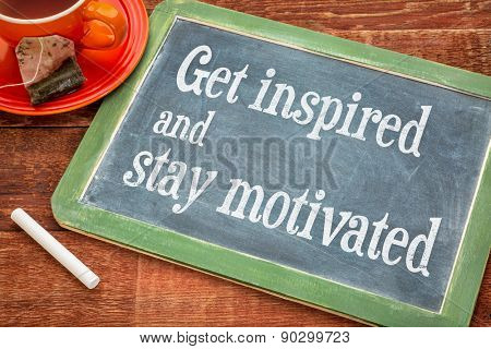 get inspired and stay motivated - motivational text on a slate blackboard with chalk and cup of tea