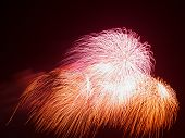 stock photo of night-blooming  - spectacular beautiful bright fireworks in the form of red and orange flowers bloom in the night black sky - JPG