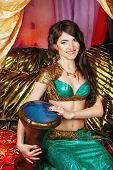 image of harem  - Sexy oriental beauty plays the tabla pleasant melody - JPG