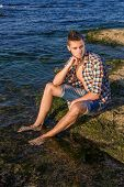 image of nearly nude  - Attractive young fashion sexy man sitting on a rock near the sea water - JPG