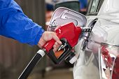 stock photo of gasoline station  - Closeup of man pumping gasoline fuel in car at gas station - JPG