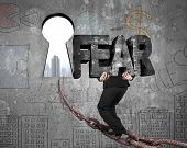 stock photo of keyholes  - Man carrying big 3D fear concrete word walking on old iron chain toward keyhole door with urban scene view and business concept doodles wall background - JPG