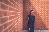 pic of tunic  - Young handsome Asian model dressed in black tunic posing with a brick wall in background - JPG