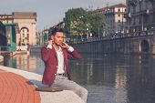 stock photo of blazer  - Young handsome Asian model dressed in red blazer sitting by an artificial basin - JPG