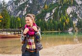 picture of pier a lake  - A fit sporty brunette smiling and readjusting her scarf on the shore of Lake Bries - JPG