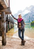 stock photo of pier a lake  - A smiling brunette woman is relaxing standing by a wooden pier on the shore of Lake Bries - JPG