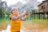 foto of pier a lake  - A young blonde girl standing on the shores of Lake Bries is smiling while holding a digital camera up - JPG