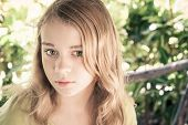 stock photo of little girls photo-models  - Closeup outdoor portrait of beautiful blond Caucasian teenage girl in a park with natural light vintage toned photo filter effect - JPG