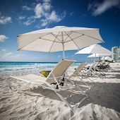 foto of caribbean  - Caribbean beach with sun umbrellas and beds Cancun Mexico - JPG