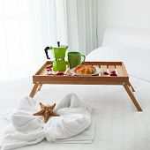 foto of bed breakfast  - Breakfast wooden tray with coffee percolator and croissant on bed decorated starfish on white towel - JPG