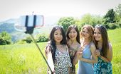 stock photo of stick  - group of girls making selfie with selfie stick - JPG