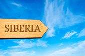 pic of siberia  - Wooden arrow sign pointing destination SIBERIA RUSSIA against clear blue sky with copy space available - JPG