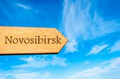 stock photo of novosibirsk  - Wooden arrow sign pointing destination NOVOSIBIRSK RUSSIA against clear blue sky with copy space available - JPG