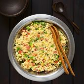stock photo of sweet-corn  - Vegetarian couscous salad made with bell pepper tomato cucumber red onion and sweet corn kernels served in salad bowl with rustic bowls and wooden spoons on the side - JPG