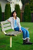 picture of biracial  - Young biracial teen girl enjoying outdoors on park bench - JPG