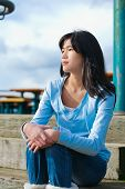 foto of biracial  - Young biracial teen girl in blue shirt and jeans sitting on wooden steps outdoors on overcast cloudy day - JPG