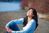 picture of biracial  - Young biracial teen girl in blue shirt and jeans sitting along rocky lake shore on bright overcast day outdoors - JPG