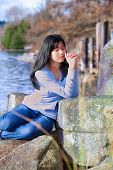 foto of biracial  - Young biracial teen girl in blue shirt and jeans quietly sitting outdoors leaning on rocks praying  - JPG