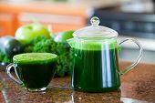 image of kale  - Glass cup of green vegetable juice on kitchen counter made with kale spinach lime apple cucumber.