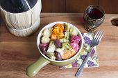 stock photo of kalamata olives  - Colorful Italian pasta dish served with artichoke hearts and kalamata olives in a ceramic bowl accompanied by a glass of Chianti wine for dinner or lunch - JPG