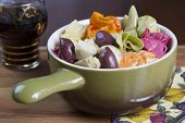 foto of kalamata olives  - Colorful Italian pasta dish served with artichoke hearts and kalamata olives in a ceramic bowl accompanied by a glass of Chianti wine for dinner or lunch - JPG