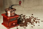 foto of wooden box from coffee mill  - Coffee bean grinder is on the burlap sack background - JPG
