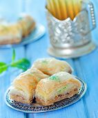 stock photo of dessert plate  - Baklava Turkish dessert on metal plate and on a table - JPG