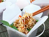 stock photo of chinese food  - Take away egg noodles on chopsticks in a take away container - JPG