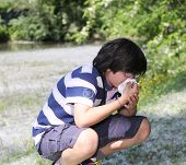 stock photo of allergy  - young boy with pollen allergy with white handkerchief - JPG