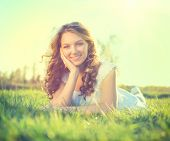 stock photo of grassland  - Beauty Romantic Girl lying on summer field Outdoors - JPG
