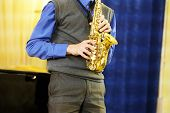 picture of saxophone player  - The performer plays a saxophone during a concert - JPG