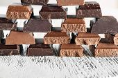 stock photo of food pyramid  - Pyramid of squared chocolate on wooden table - JPG