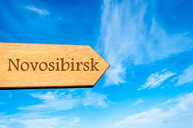 picture of novosibirsk  - Wooden arrow sign pointing destination NOVOSIBIRSK RUSSIA against clear blue sky with copy space available - JPG