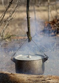 image of smut  - Cooking in sooty cauldron on campfire at spring forest - JPG
