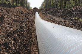 stock photo of pipeline  - A uncovered pipeline construction site with soil around - JPG