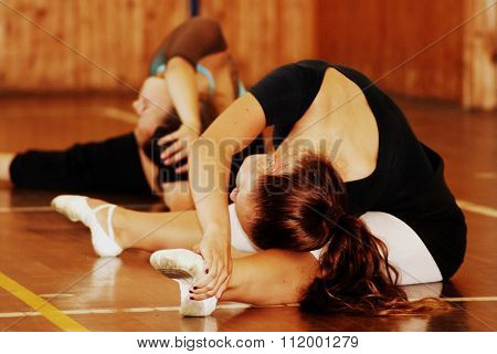Ballet dancers warm up on gymnasium floor