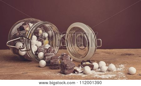 Chocolates In Glass Jar On Wooden Background