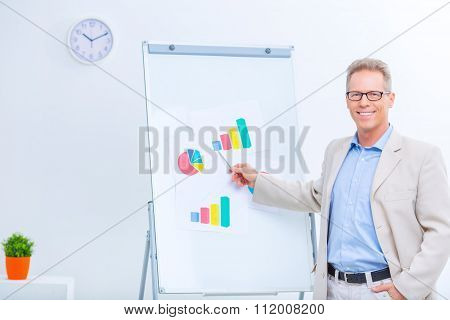 Smiling businessman working with charts.