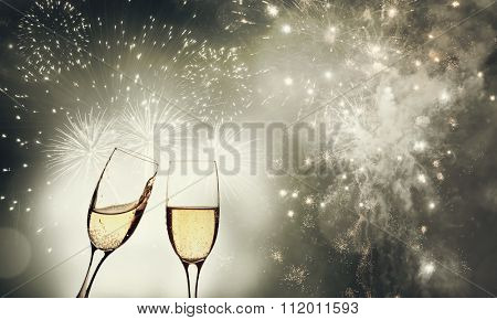 Glasses with champagne against fireworks and holiday lights