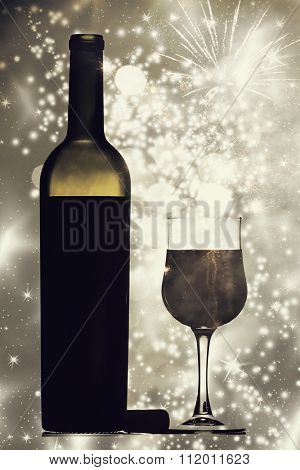 Glass and bottle of red wine against holiday lights