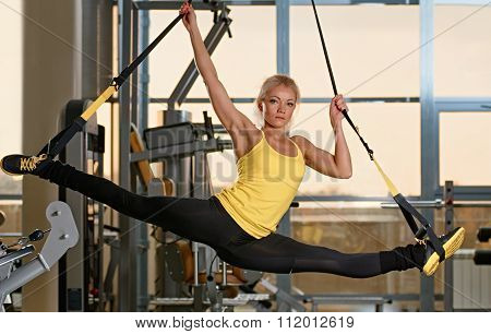 young woman does splits with trx fitness