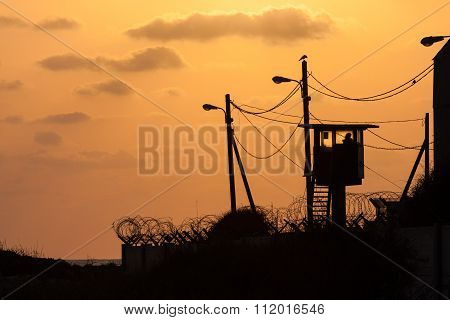Silhouette Of Army Watchtower Behind Barbed Wires