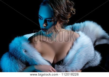 Luxury woman with deep neckline posing in fur