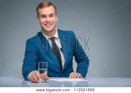 Smiling newsman holding a glass of water.