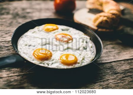 Fried Egg In A Frying Pan On A Wooden Table