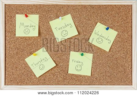 Yellow Sticky Notes With Weekdays And Smileys Sticked On Corkboard