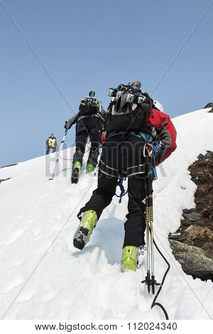 Team Ski Mountaineers Climbing On The Mountain On A Rope